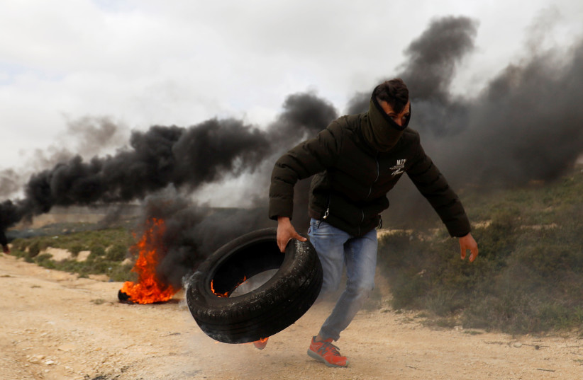 A Palestinian moves a tire during clashes with Israeli troops at a protest against Jewish settlements in the village of Oref, in the West Bank (photo credit: MOHAMAD TOROKMAN/REUTERS)