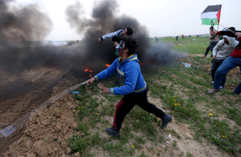 Palestinians hurl stones at Israeli troops during a protest at the Israel-Gaza border fence, in the southern Gaza Strip February 15, 2019. (photo credit: IBRAHEEM ABU MUSTAFA / REUTERS)