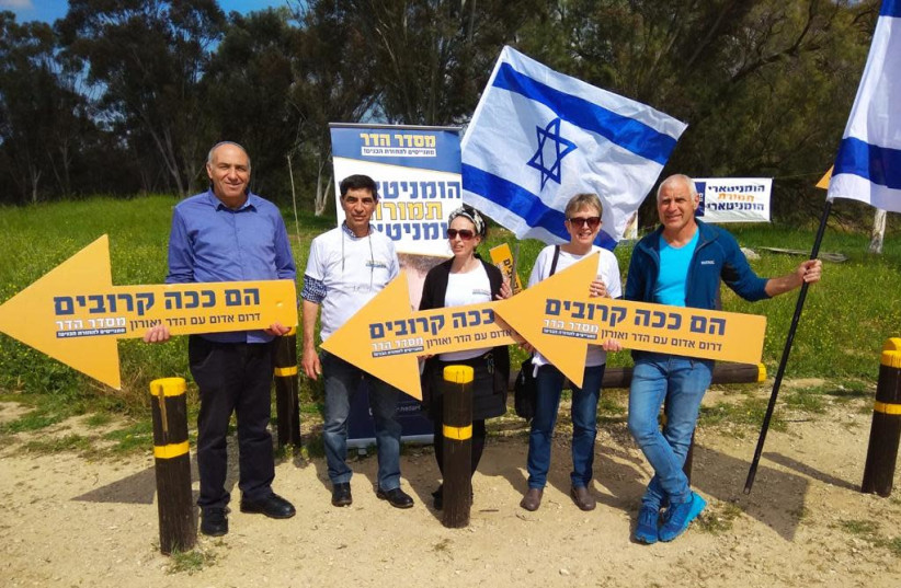 """The parents of fallen IDF Lt. Hadar Goldin with Members of Knesset hold signs reading """"they're this close"""" at a protest near the Gaza border, calling for the bodies of their son and another IDF soldier to be returned (photo credit: MISDAR HADAR)"""