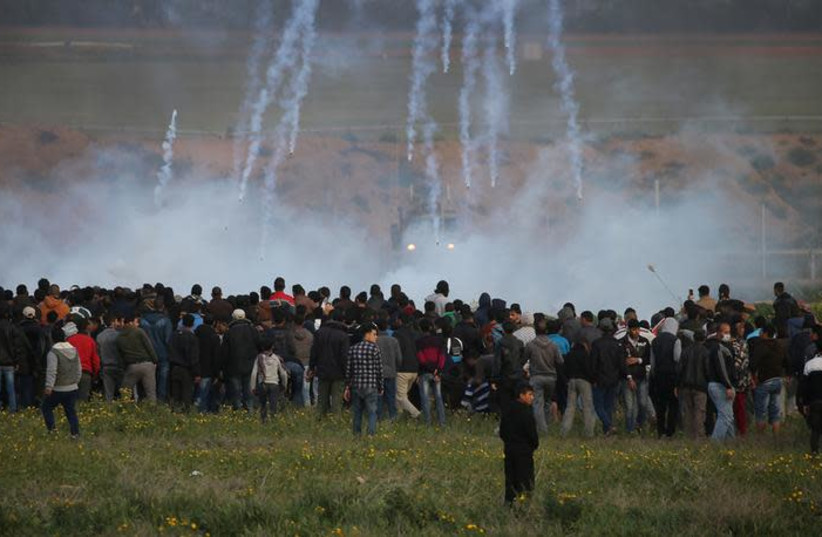 Tear gas canisters are fired by Israeli troops toward Palestinians during a protest at the Israel-Gaza border fence, in the southern Gaza Strip February 22, 2019 (photo credit: REUTERS/IBRAHEEM ABU MUSTAFA)