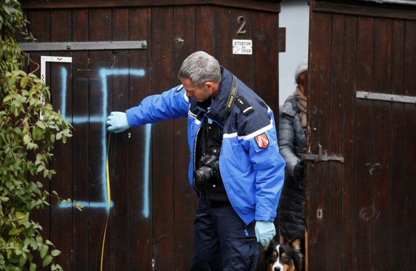 A French gendarme inspects a door that is desecrated with a swastika near the Jewish cemetery in Quatzenheim, near Strasbourg, France (photo credit: REUTERS/VINCENT KESSLER)