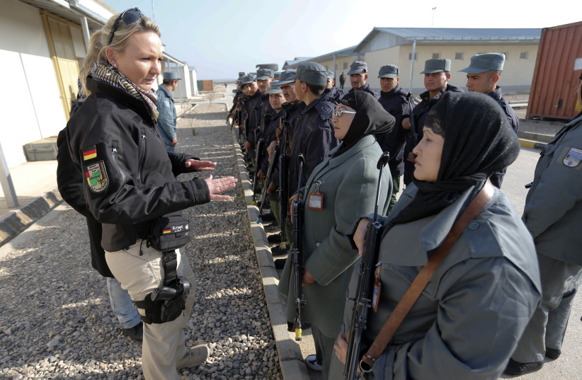 A German police instructor talks to female Afghan National Police (ANP) officers before a drill at a training centre near the German Bundeswehr army camp Marmal in Mazar-e-Sharif, northern Afghanistan December 11, 2012. German police is mentoring the training program for ANP, as part of an ongoing I (photo credit: FABRIZIO BENSCH / REUTERS)