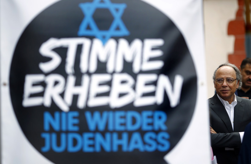 Dieter Graumann, head of Germany's Jewish community and vice president of the Jewish World Congress, stands next to a banner during a demonstration against anti-Semitism in Frankfurt, August 31, 2014 (photo credit: KAI PFAFFENBACH/REUTERS)