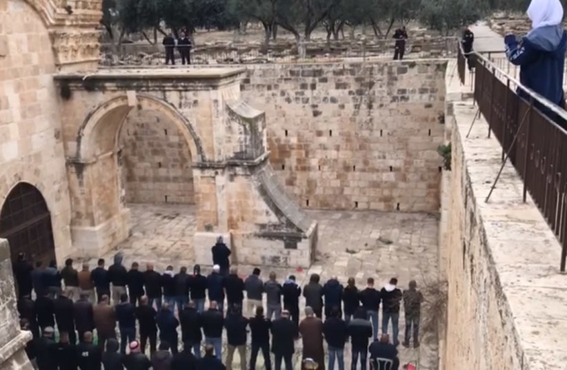 A prayer vigil at the Golden Gate patio area on the Temple Mount as police look on, February 21, 2019. A court order closed the area after the Waqf was cause conducting unauthorized construction and excavations (photo credit: screenshot)