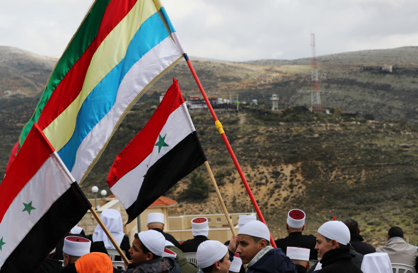 Members of the Druze community holds Syrian and Druze flags as they sit facing Syria, during a rally marking the anniversary of Israel's annexation of the Golan Heights in the Druze village of Majdal Shams. February 14, 2019.  (photo credit: AMMAR AWAD / REUTERS)