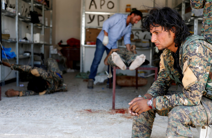 A Syrian Democratic Forces (SDF) fighter sits as medics treat his comrades injured by sniper fired by Islamic State militants in a field hospital in Raqqa, Syria, June 28, 2017. (photo credit: GORAN TOMASEVIC/REUTERS)