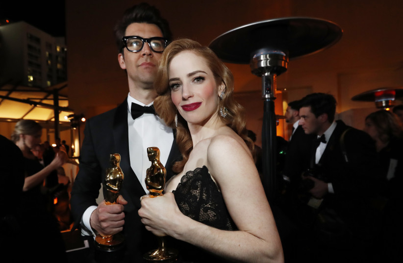 """Guy Nattiv and Jaime Ray Newman with their awards for Best Live Action Short Film for the film """"Skin,"""" February 24, 2019 (photo credit: MARIO ANZUONI/REUTERS)"""