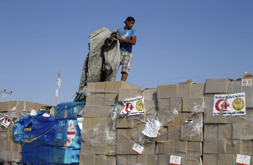 A Palestinian man checks a truck loaded with medical aid after entering Gaza at the Kerem Shalom crossing, in Rafah in the southern Gaza Strip August 28, 2014. An open-ended ceasefire in the Gaza war held on Wednesday as Prime Minister Benjamin Netanyahu faced strong criticism in Israel over a costl (photo credit: IBRAHEEM ABU MUSTAFA/REUTERS)