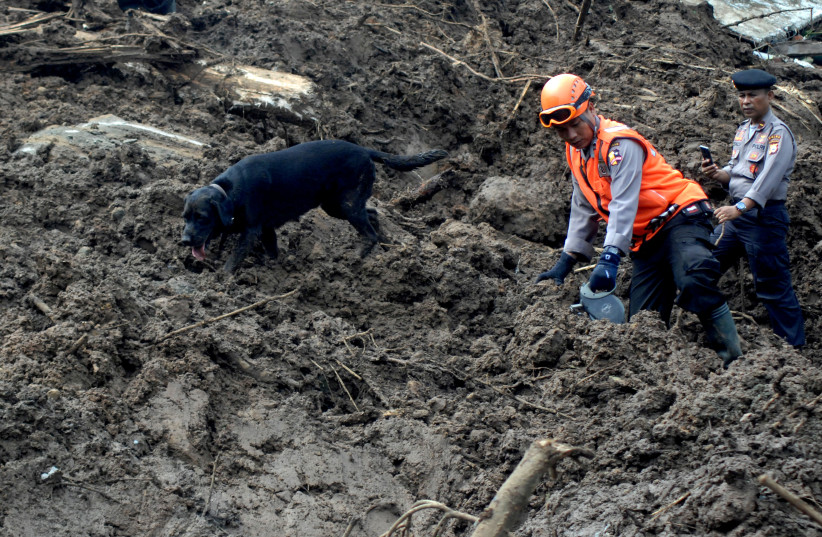 Indonesian police officers walk with dog as they search for victims following landslides in Gowa, South Sulawesi, Indonesia, January 26, 2019 in this photo taken by Antara Foto. Picture taken January 26, 2019 (photo credit: ANTARA PHOTO AGENCY VIA REUTERS)