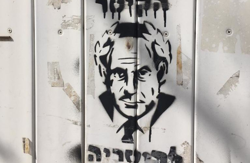 Graffiti spotted near demonstration protesting indictment charges against Benjamin Netanyahu (photo credit: YVETTE J. DEANE)