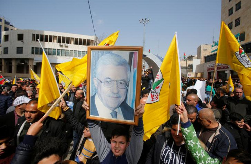 Palestinians take part in a Fatah rally in support of president Mahmoud Abbas, in the Palestinian Authority controlled side of Hebron, February 24, 2019 (photo credit: REUTERS/MUSSA QAWASMA)