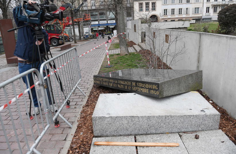 A cameraman films the memorial stone marking the site of Strasbourg's Old Synagogue, which was destroyed by the Nazis in World War II, after it was vandalised overnight on March 2, 2019 in Strasbourg, eastern France. The synagogue, which was the Jewish community's main place of worship in the city,  (photo credit: FREDERICK FLORIN/AFP)