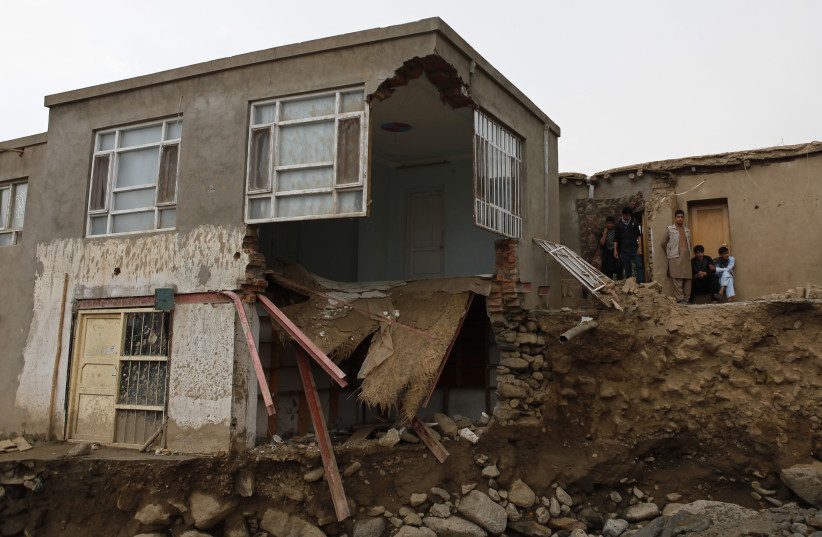 Afghans stand near a destroyed house after floods in the Shakar Dara district of Kabul August 11, 2013.At least 22 people in Afghanistan were killed and farmland was damaged when flash floods hit a plain near the capital, officials said on Sunday (photo credit: REUTERS)