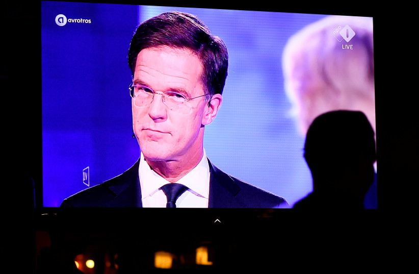 """Locals sit as Dutch Prime Minister Mark Rutte of the VVD Liberal party and Dutch far-right politician Geert Wilders of the PVV party take part in the """"EenVandaag"""" debate, shown live on television at a bar in The Hague, Netherlands March 13, 2017 (photo credit: DYLAN MARTINEZ/REUTERS)"""