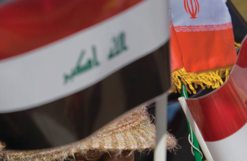 IRAN AND Iraqi flags held aloft by a woman. (photo credit: REUTERS)