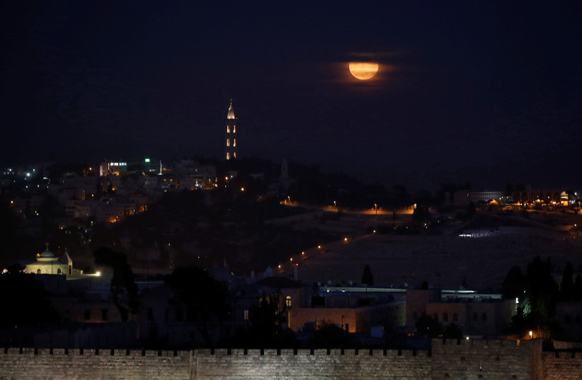 """A """"super moon"""" rises behind the Mount of Olives cemetery in Jerusalem looking towards Maale Adumim, November 14, 2016 (photo credit: RONEN ZVULUN / REUTERS)"""