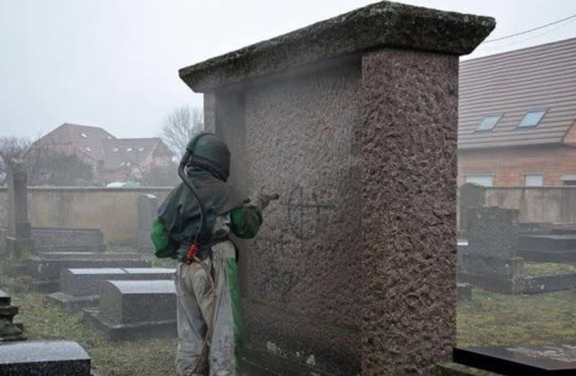A worker removes antisemitic graffiti at a Jewish cemetery in France, March, 2019 (photo credit: FRANCE 3 ALSACE AND THE LOWER RHINE CONSISTORY)