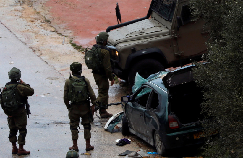 Israeli forces stand at the scene of a car ramming in the West Bank that injured two soldiers, March 4, 2019 (photo credit: REUTERS/MOHAMAD TOROKMAN)