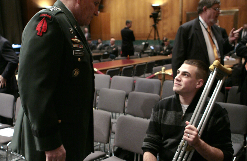 U.S. Army Chief of Staff Gen. Peter Schoomaker (L) talks with amputee Aaron Schoenfeld, a Marine veteran from Navarre, Florida, at a hearing by the Senate Armed Services Committee on Capitol Hill in Washington about conditions at Walter Reed Army Medical Center March 6, 2007. Schoomaker's brother, M (photo credit: REUTERS)