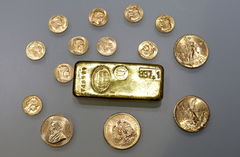 A gold ingot and gold coins are seen in this illustration picture taken November 17, 2017. (photo credit: ERIC GAILLARD/REUTERS)