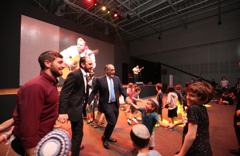 Jewish children dance with South Africa's Chief Rabbi Warren Goldstein as Alex Clare entertains the crowd on Sunday evening. (photo credit: GUY LERNER)