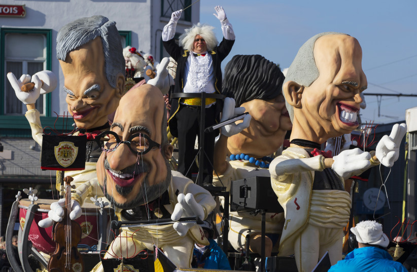 Giant figures depicting Belgian Prime Minister Charles Michel (C) and other politicians are seen during the 87th carnival parade of Aalst February 15, 2015. The Aalst Carnival, which is inscribed on the Representative List of the Intangible Cultural Heritage of Humanity, often shows informal groups  (photo credit: YVES HERMAN / REUTERS)