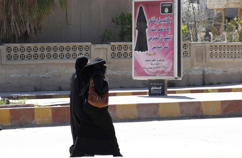Veiled women walk past a billboard urging women to wear a hijab in Raqqa(REUTERS/Stringer) (photo credit: REUTERS/STRINGER)