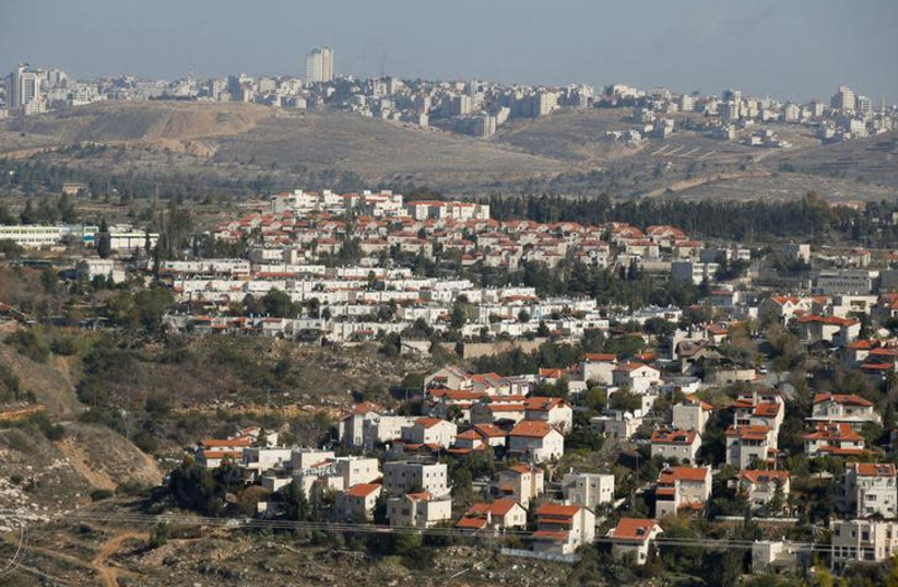 Houses are seen in the Israeli community of Givat Zeev (bottom) with the Palestinian Authority city of Ramallah in the background, December 29, 2016 (photo credit: BAZ RATNER/REUTERS)
