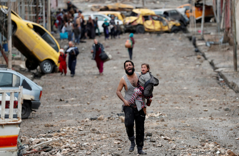 A man cries as he carries his daughter while walking from an Islamic State-controlled part of Mosul towards Iraqi special forces soldiers during a battle in Mosul, Iraq. (photo credit: GORAN TOMASEVIC/REUTERS)