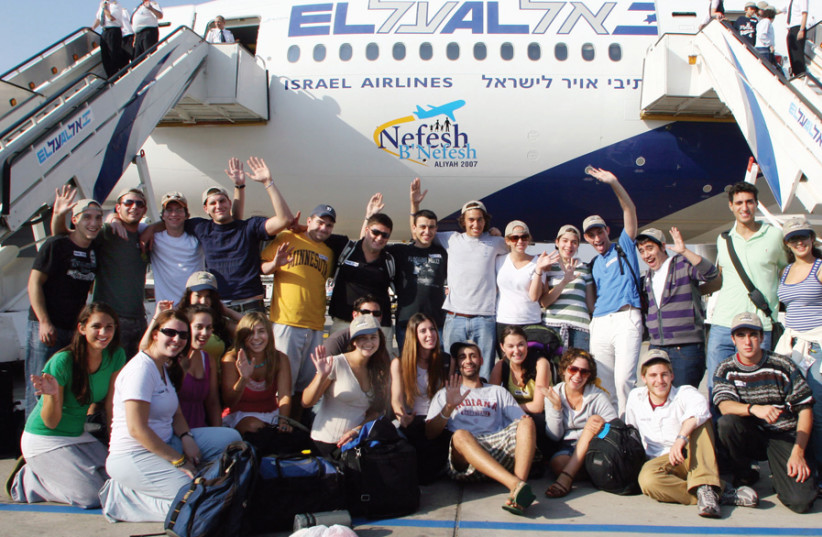 NEW 'OLIM' wave excitedly after arriving in Israel on a Nefesh B'Nefesh charter flight. (photo credit: Wikimedia Commons)