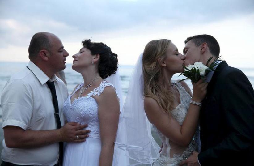 Couples kiss during a mass wedding at coastal city of Larnaca (photo credit: REUTERS/YIANNIS KOURTOGLOU)