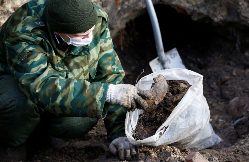 "A soldier from a special ""search battalion"" of Belarus Defence Ministry takes part in the exhumation of a mass grave containing Jewish victims. Brest, Belarus February 2019. (photo credit: VASILY FEDOSENKO / REUTERS)"