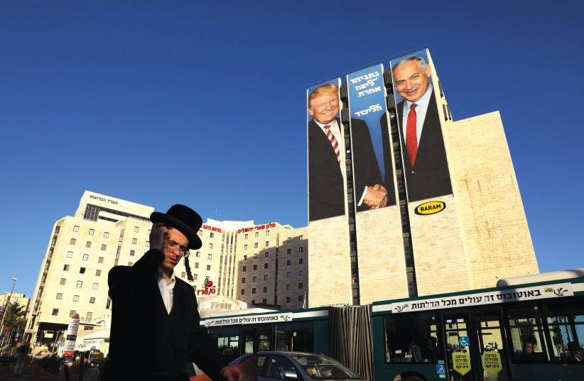 A MAN walks past a Likud election campaign billboard, depicting US President Donald Trump with Prime Minister Benjamin Netanyahu and the words, 'Netanyahu. A different league' (photo credit: AMMAR AWAD / REUTERS)
