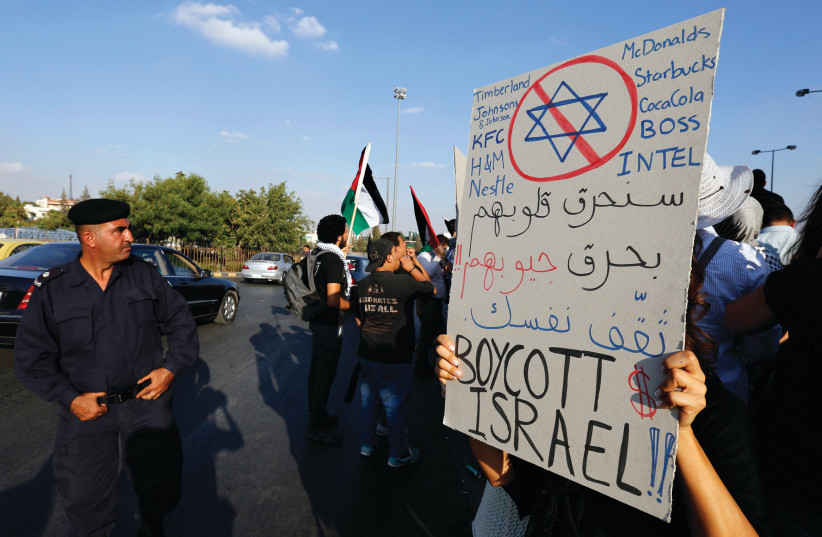 A JORDANIAN policeman stands guard in front of the prime minister's office in Amman as a protester holds a placard urging the boycott of Israel. The sign reads, 'We will burn their hearts by burning their pockets, educate yourself.' (photo credit: MUHAMMED HAMED / REUTERS)