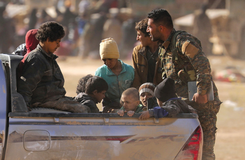 CHILDREN FROM THE Yazidi community, who were recently freed after being captured by Islamic State fighters, ride on a back of a truck near Baghouz, Syria, earlier this week (photo credit: RODI SAID / REUTERS)