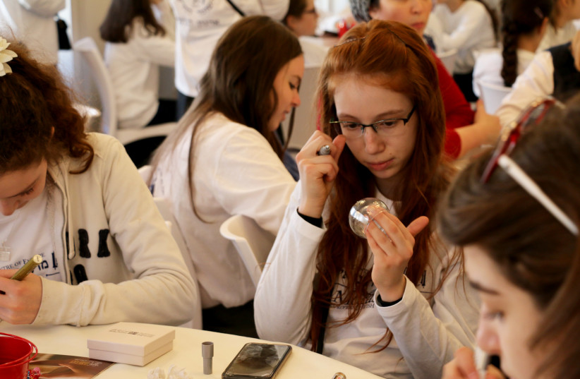 Bat mitzvah age girls decorate Shabbat candlestick holders during the Rabbinical Center of Europe trip to Israel, March 2019 (photo credit: Courtesy)