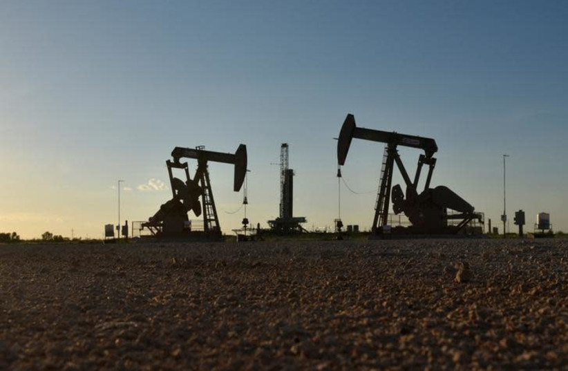 Pump jacks operate in front of a drilling rig in an oil field in Midland, Texas, in August (photo credit: REUTERS)