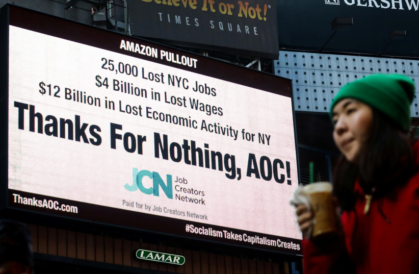 """A woman passes by an electronic billboard in Times Square displaying, """"Thanks For Nothing, AOC!"""", referencing U.S. Rep. Alexandria Ocasio-Cortez (D-NY) and the pullout of Amazon's HQ 2 in New York City, U.S., February 21, 2019 (photo credit: BRENDAN MCDERMID/REUTERS)"""