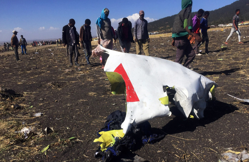 People walk past a part of the wreckage at the scene of the Ethiopian Airlines Flight ET 302 plane crash, near the town of Bishoftu, southeast of Addis Ababa, Ethiopia March 10, 2019 (photo credit: TIKSA NEGERI / REUTERS)