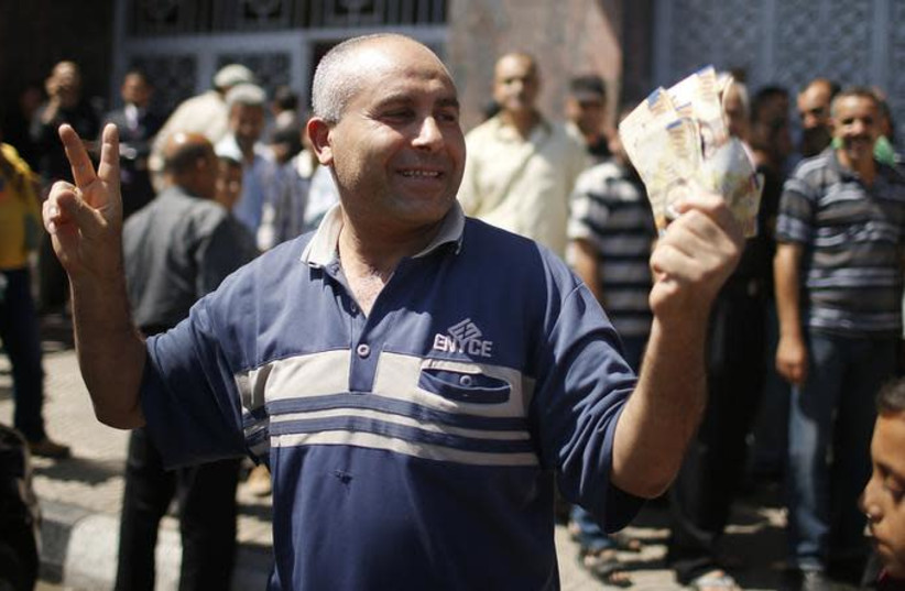 A Palestinian employee paid by the Palestinian Authority gestures as he holds money after withdrawing cash from an ATM machine outside a bank, in Gaza City (photo credit: REUTERS/MOHAMMED SALEM)