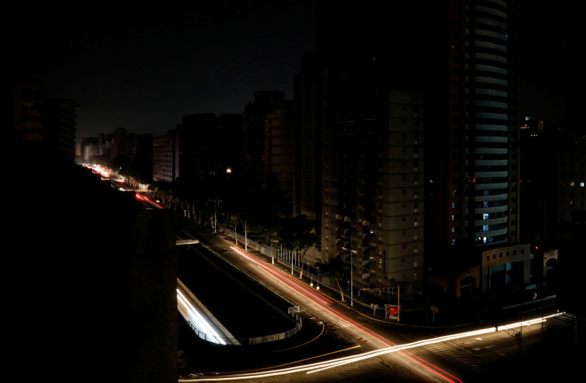 Car lights are seen on one of the main roads of the city during the second day of a blackout in Caracas, Venezuela March 9, 2019 (photo credit: REUTERS/CARLOS JASSO)