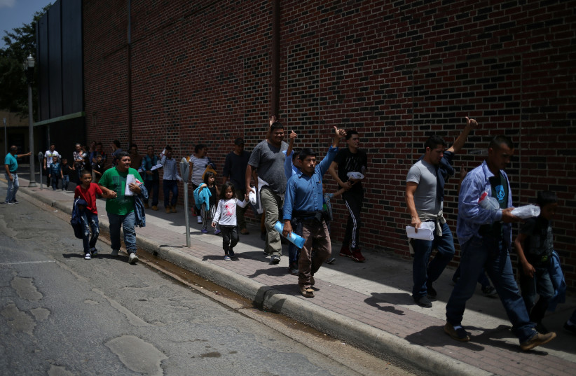 Undocumented immigrant families walk from a bus depot to a respite center after being released from detention in McAllen, Texas, U.S., July 28, 2018 (photo credit: LOREN ELLIOTT/REUTERS)