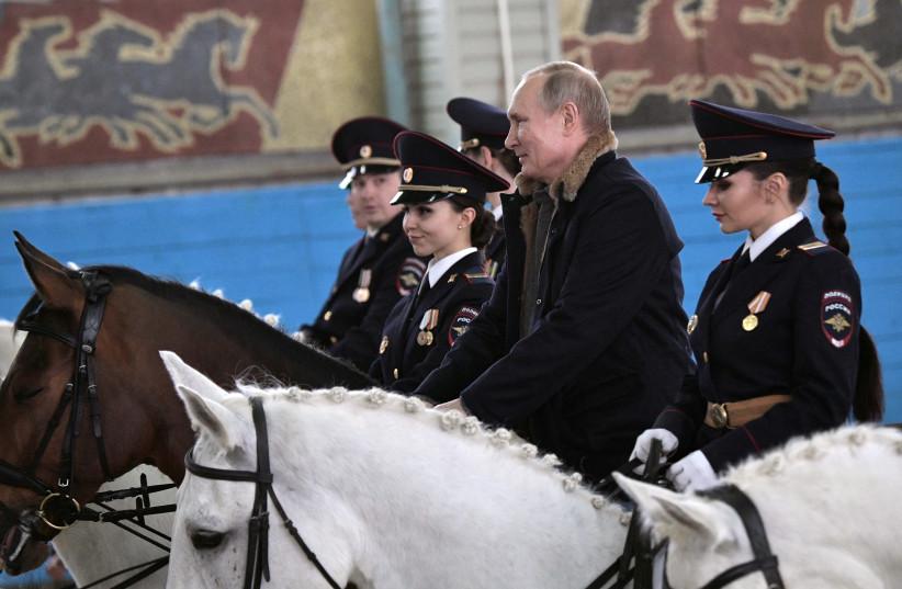 Putin meeting with Russian policewomen on Women's Day (Sputnik Photo Agency/REUTERS) (photo credit: SPUTNIK PHOTO AGENCY / REUTERS)
