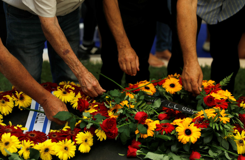 Members of the Shimon Peres's family lay flowers on his grave (photo credit: RONEN ZVULUN / REUTERS)