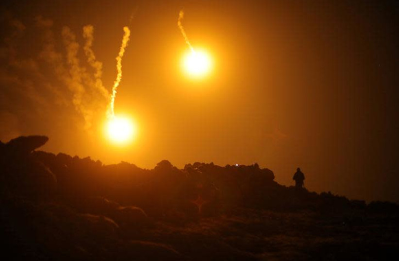 Flares are seen in the sky during fighting in the Islamic State's final enclave, in the village of Baghouz, Deir Al Zor province, Syria March 11, 2019 (photo credit: REUTERS/RODI SAID)