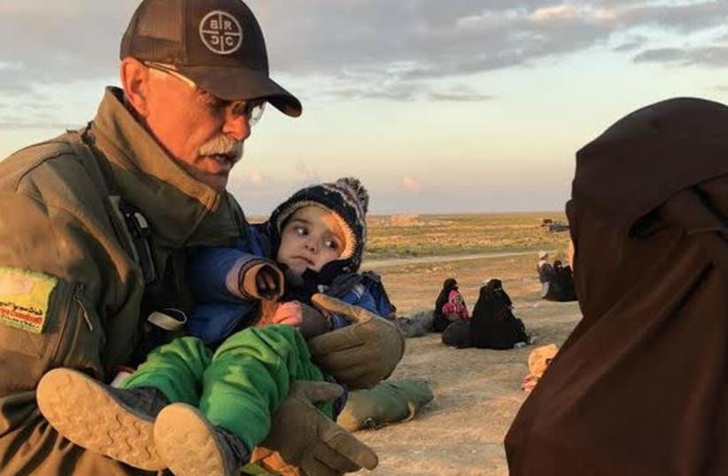 Paul Curtis Bradley carries a child near Baghuz  (photo credit: COURTESY FREE BURMA RANGERS)