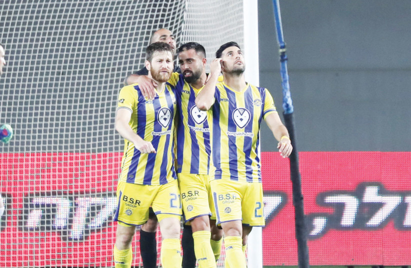 MACCABI TEL AVIV players celebrate after an 81st-minute goal by Avi Rikan (right), a tally which helped the yellow-and-blue complete a comeback from a 1-0 deficit and defeat Bnei Yehuda 2-1 on Monday night to close out the Premier League regular season.  (photo credit: DANNY MARON)