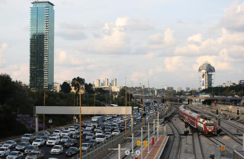 Cars drive on a highway as a train enters a station in Tel Aviv, Israel November 25, 2018 (photo credit: REUTERS/CORINNA KERN)