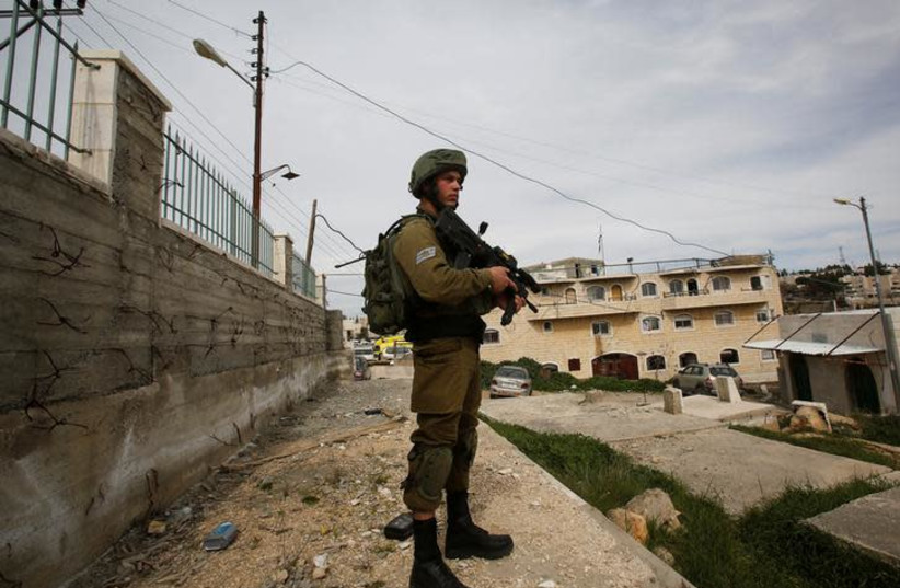An Israeli soldier stands guard in Hebron (photo credit: REUTERS/MUSSA QAWASMA)