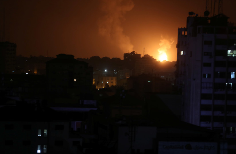 Smoke and flame are seen during an Israeli air strike in Gaza (photo credit: MOHAMMED SALEM/ REUTERS)